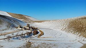 Schneebedecktes Landschaftsgebiet Mingsha-Berg und Mondsichel-Quelle