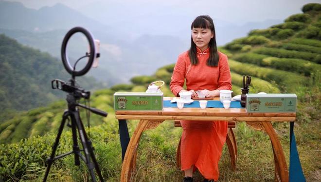 Mädchen im traditionellen Kostüm präsentieren chinesischen Tee per Liveübertragung