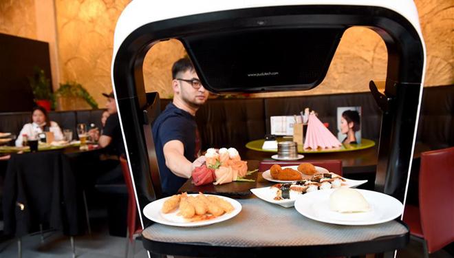 Robot liefert Mahlzeiten an Kunden im asiatischen Restaurant in Wien