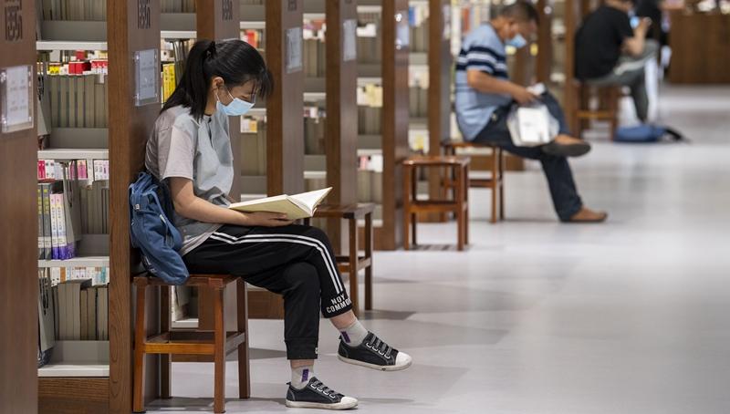 Menschen lesen Bücher in Bibliothek während Feiertage zum Drachenbootfest