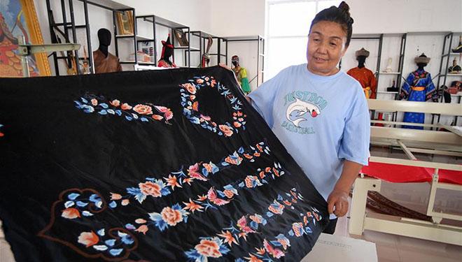 Arbeiterinnen stellen mongolische ethnische Kleidungen in einem Workshop zur Armutsbekämpfung in Chinas Innere Mongolei her