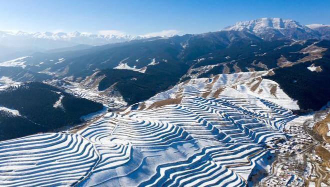 Schneebedeckte Terrassenfelder in bergigem Gebiet in Gansu