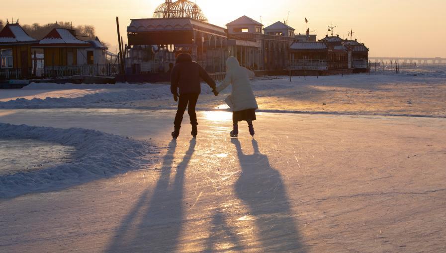 Menschen laufen Schlittschuh auf Eis in Harbin