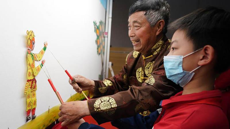 Künstler spielen traditionelle Schattenspiel an Mittelschule in Hebei